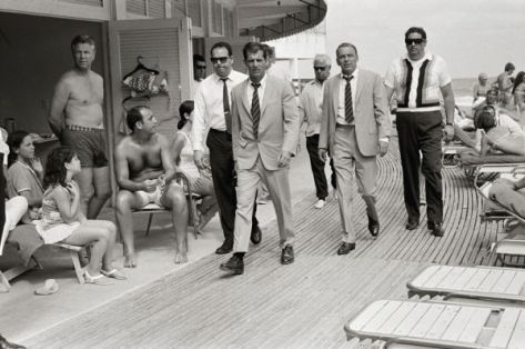 Frank Sinatra, with his minders and his stand in (who is wearing an identical outfit to Sinatra), arriving at Miami beach while filming, 'The Lady In Cement', 1968