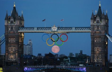 Full moon rises through the Olympic rings at Tower Bridge in London