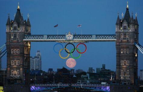 Full moon rises through the Olympic rings at Tower Bridge in London