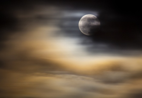 The January 'Wolf' Full Moon through a mixture of clouds and smoke from a burning tyre dump, which was visible from Space.
