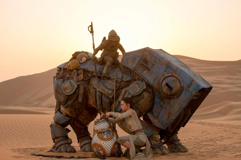Rey (Daisy Ridley) meets up with BB-8 while cutting him free from a fellow scavenger's net. But what is that large creature — and who is riding atop it?